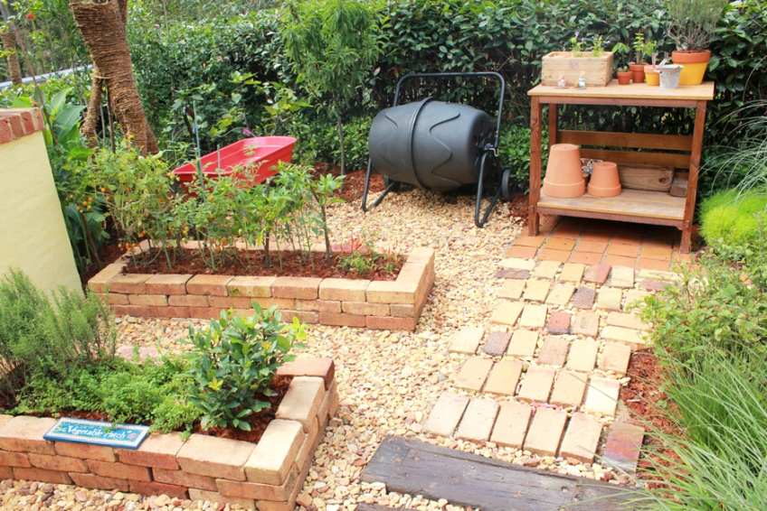 The Gardening Area Features Brick Beds And A Table Accessible Through Walkway Covered With Wooden Beams